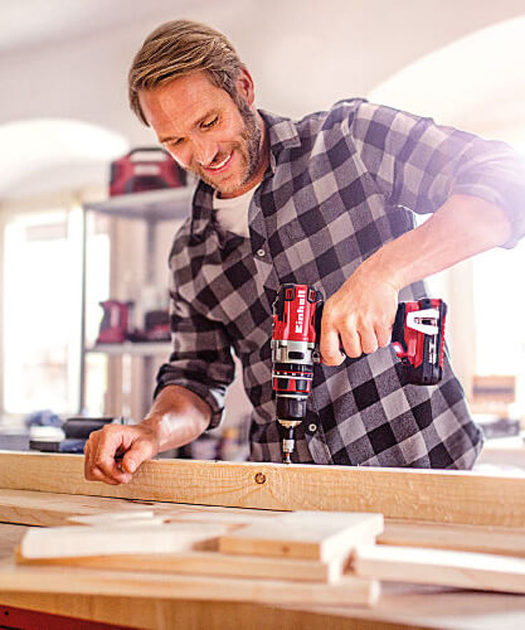 A DIY enthusiast screws wood parts together with a Einhell Power X-Change cordless screwdriver.